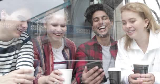 Šťastné multirasové přátele, kteří se dívají na smartphone v kavárně a smějí se. Gro