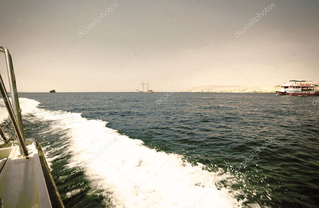 Foam trail from a speed yacht in the Gulf of Aqaba, on the border of Israel, Jordan and Egypt. Retro style.