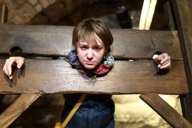 Portrait of woman in a wooden pillory