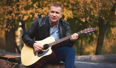 Man playing guitar in the autumn park. Outdoors portrait
