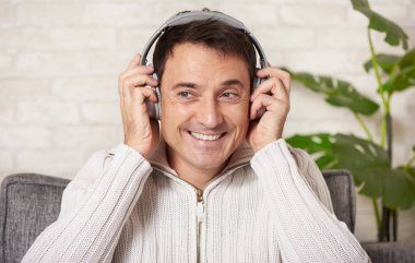 Happy man is listening to music at home
