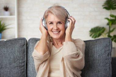 Happy senior woman is listening to music