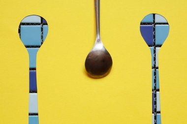 Abstract concept. One metal spoon with two spoons gap against yellow paper