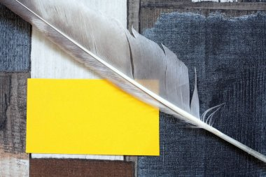 Vintage still life with quill pen near yellow blank paper