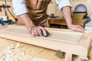 detail of caucasian carpenter at work in a workshop
