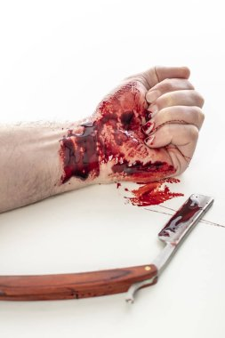 detail on bloody wrist and dirty razor, concept of suicide