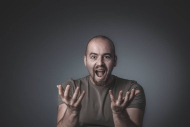 studio shot of a man with a surprised and enthusiastic expressio
