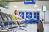 Mladá žena v mezinárodní letiště pomocí mobilního telefonu při čekání na její let