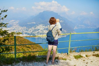 Woman with little girl enjoying scenic view to the lake Lugano from mountain San Salvatore in Lugano, canton of Ticino, Switzerland. Mother with baby on a view point. Travelling with kids