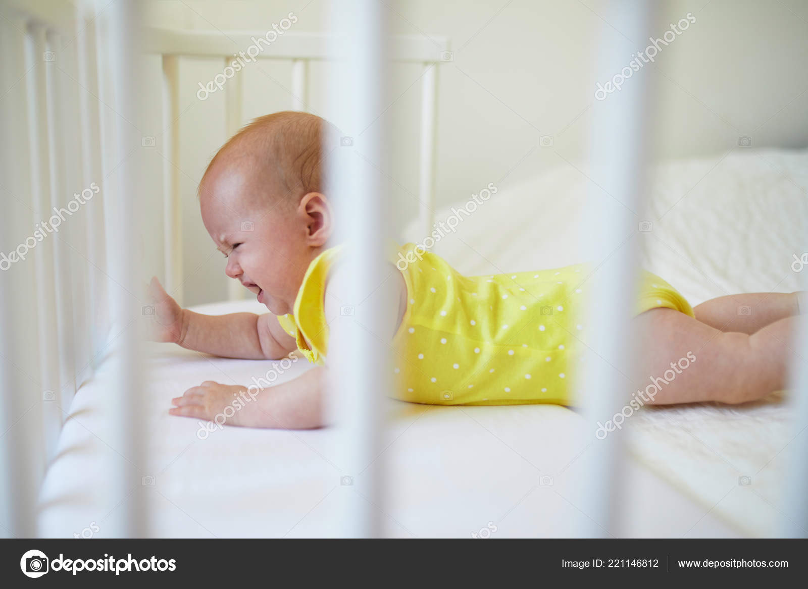 Adorable baby girl lying in co sleeper crib attached to parents bed and crying little child not wanting day nap in cot infant kid in sunny nursery
