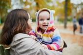 Donna invecchiata centrale felice con la neonata autunno soleggiato giorno nel parco. Nonna, divertendosi con la nipote allaperto. Attività autunno con i bambini