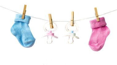 Pink and blue baby socks and pacifiers on the clothesline