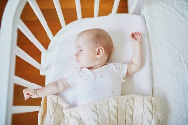 Baby sleeping in co-sleeper crib attached to parents' bed