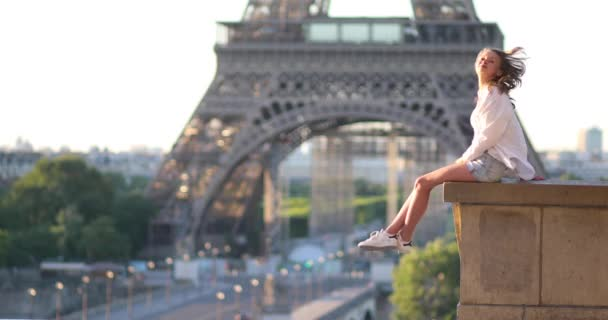 Beautiful young girl in Paris near the Eiffel tower at morning