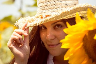 Cute girl in the field full of sunflowers. young beautiful woman on blooming sunflower field in summer