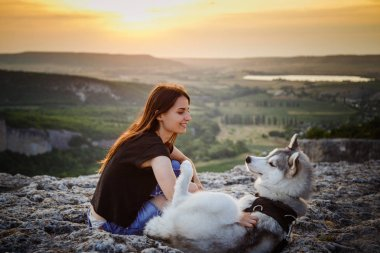 Beautiful girl plays with a dog, grey and white husky, in the mountains at sunset