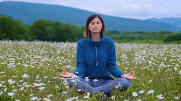 Asiatka cvičí nebo cvičí jógu na sedmikráskovém poli, Lotus pózuje na meditačním sezení. Krásná krajina, přírodní zázemí. Mezinárodní den jógy. na post pandemické znovuotevření pobytu