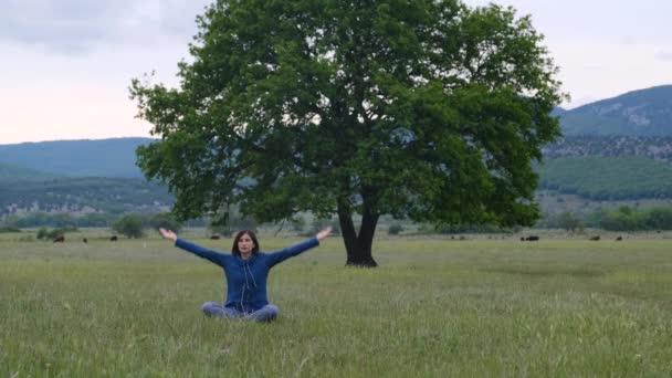 Žena na podložce na jógu k odpočinku na poli poblíž osamělého dubu. jóga venku v přírodě. Namaste Lotus pózuje. Meditace a relax
