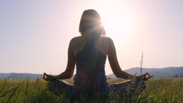 Mladá Asiatka medituje při západu slunce na poli. Žena cvičení představují životně důležité a meditace pro fitness životní styl klubu na venkovním přírodním pozadí. Zdravá a jóga koncepce