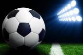 Fotografie Soccer ball on green stadium, arena in night illuminated bright spotlights