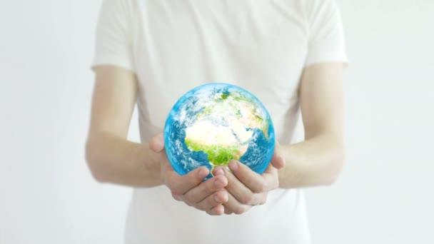 Ruce drží planetu. Mladé dospělé ruce držící zeměkouli na bílém pozadí. Koncepce ochrany.