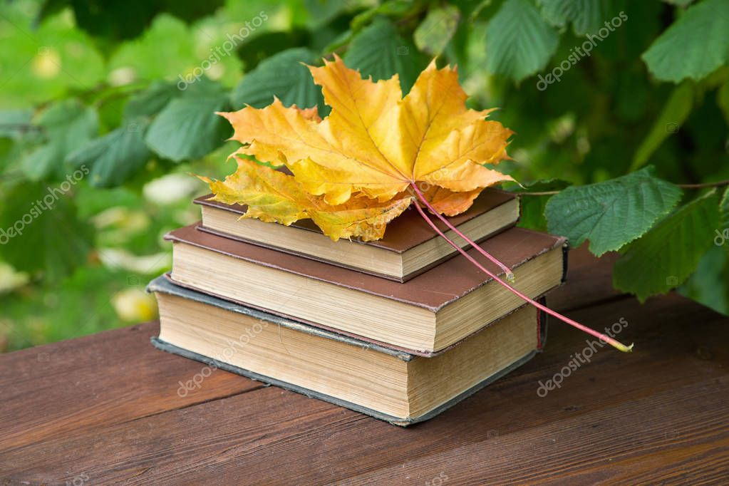 old books with yellow maple leaves on a rustic table