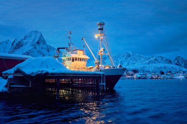 Fishing boat in Reine village at night. Lofoten islands, Norway