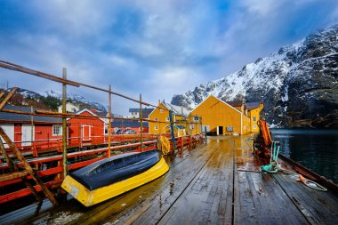 Nusfjord authentic  fishing village in winter with red and yellow rorbu houses. Lofoten islands, Norway stock vector