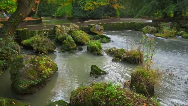 Mnichov anglická zahrada Englischer garten park. Podzimní barvy na stromech a listí a tekoucí řeka. Mnichov, Bavorsko, Německo