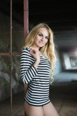 Sexy young blond woman in striped blouse posing near iron fence