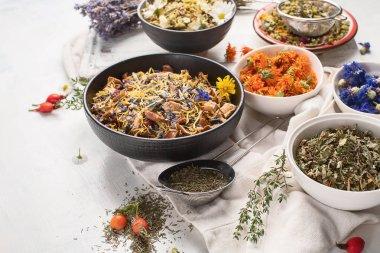 Various herbal tea ingredients in bowls on white background