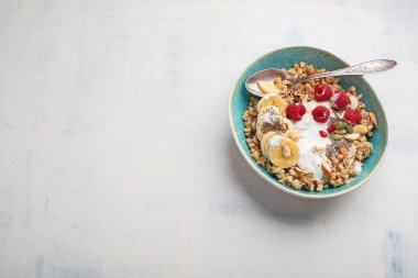 Bowl of granola with yogurt and fresh berries for healthy breakfast. Top view with copy space