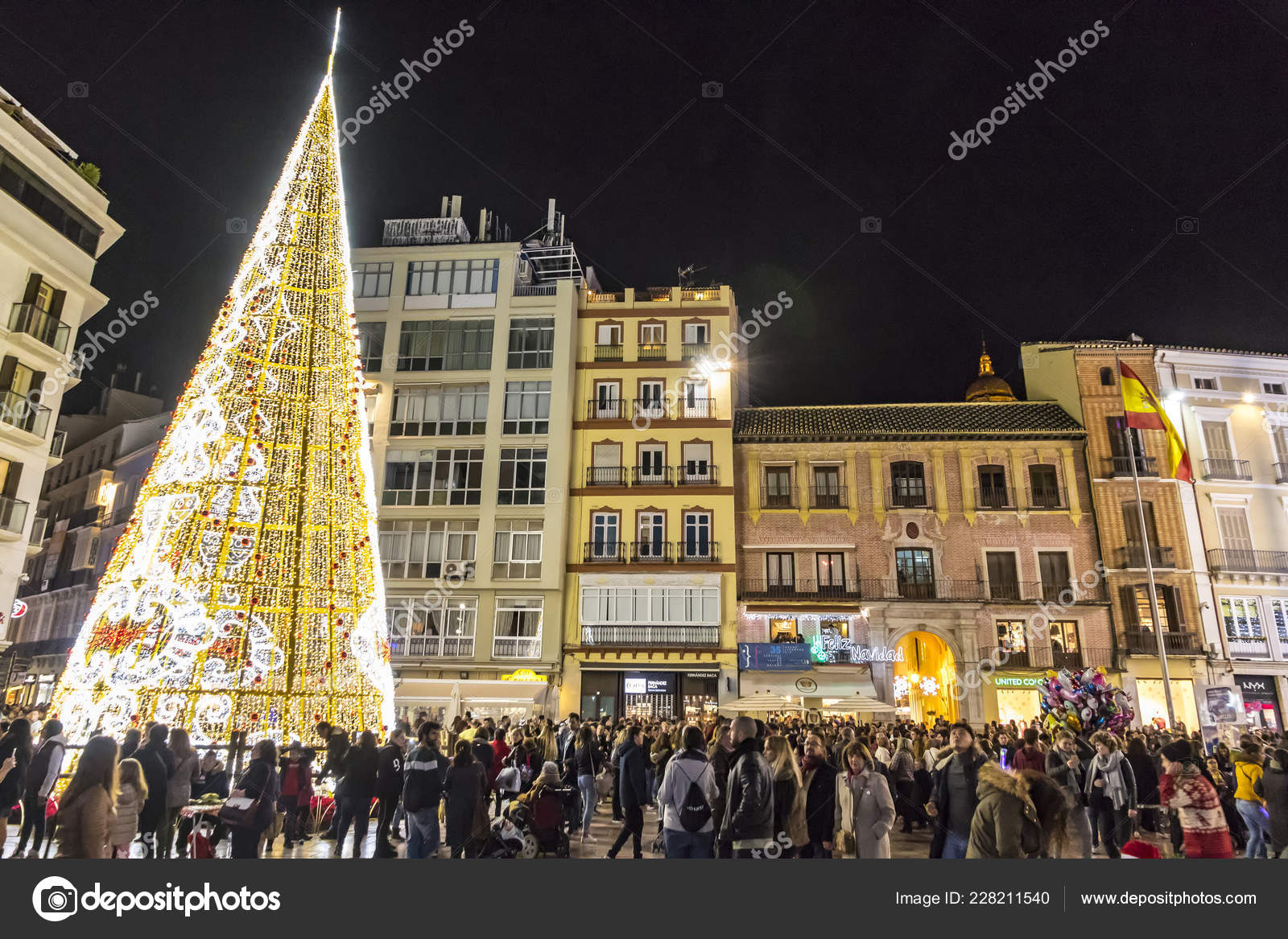MALAGA, SPAIN - DECEMBER 9, 2017: Crowds of people walking near the decorated Christmas Tree on Plaza de la Constitucion in center of Malaga city, ...