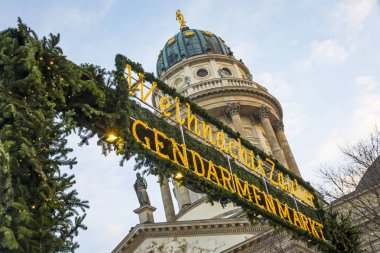 Entrace welcome sign of Gendarmenmarkt Christmas Market in Berlin, Germany. One of the most famous Christmas market in Europe. French Church (Franzosischer Dom) on background