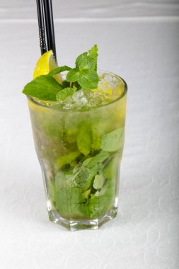 Cold Mojito cocktail on white table
