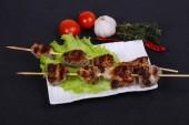 Vepřové kebab špejle na talíři se salátovými listy a rajčaty podávané tymiánem a garkikem