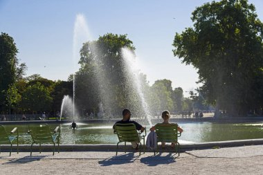 A man and a woman are resting by the pond in the Tuileries garde