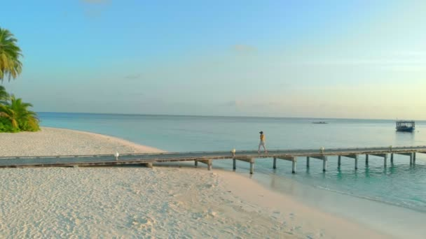 Carefree woman in summer dress walking by wooden jetty to the beach on exotic Maldivian island full of palms