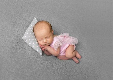 Lovely newborn girl in pink drees sleeping