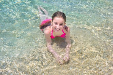 Little girl swimming in shallow water