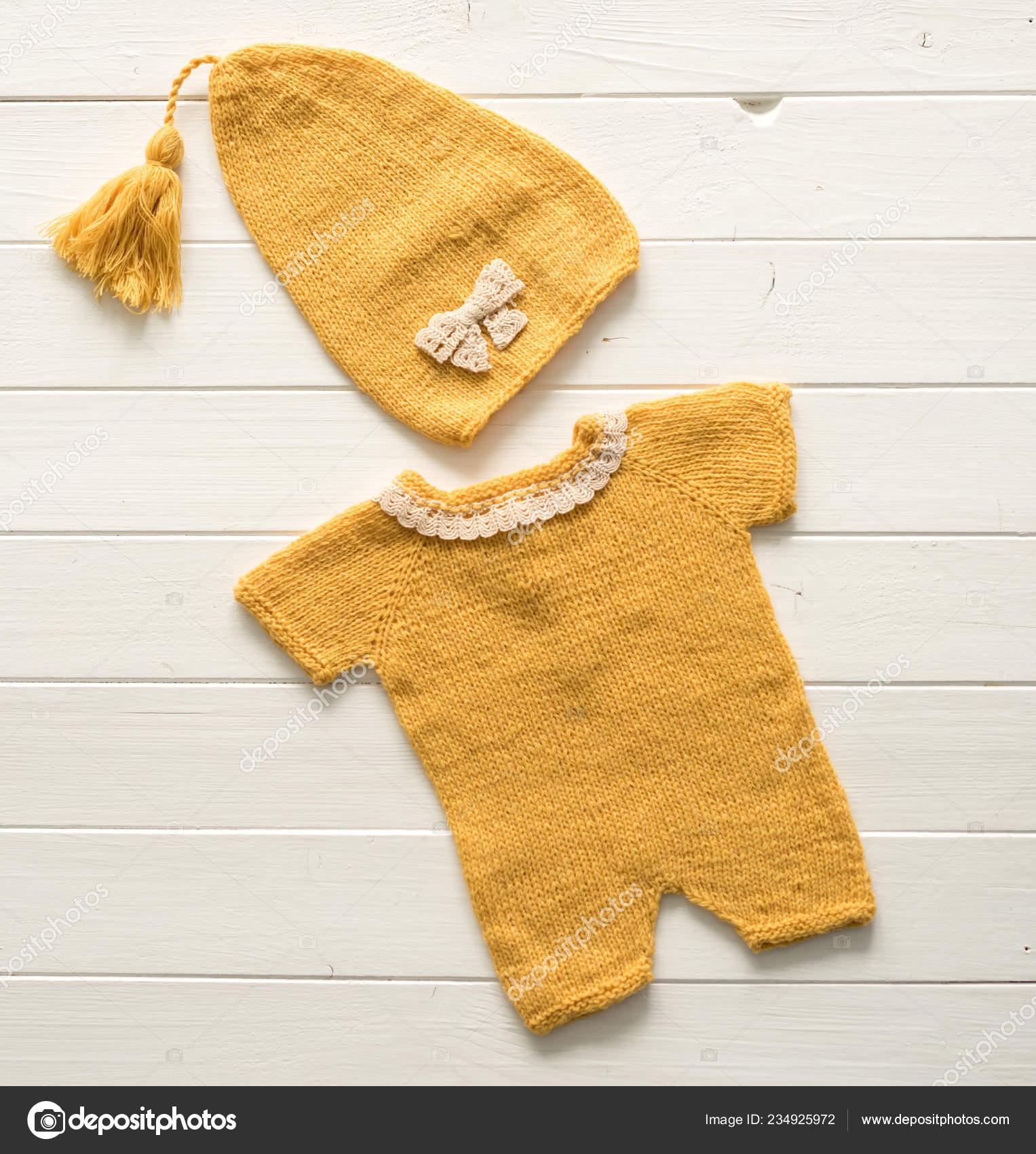d4f2e405a290 Πολύχρωμα μικρά πλεκτά ρούχα για τα μωρά που αποτελείται από το λευκό  πίνακα — Εικόνα από ...