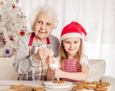Grandmother with granddaughter holding baked cookie