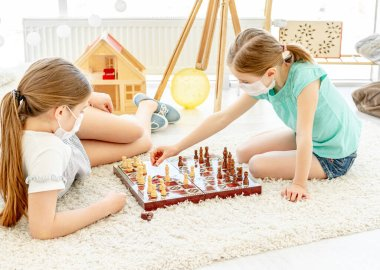 Beautiful school girls in medical masks playing chess during quarantine at home stock vector