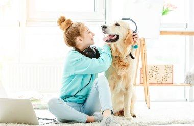 Girl putting headphones on cute dog