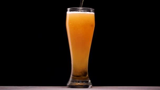 Světlé pivo nalévá do skla. Bubliny a pěny.