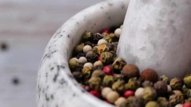 Pestle grinding peppercorn in mortar