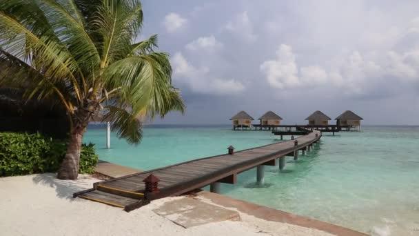 Vodní vily (bungalovy) a dřevěný most na tropické pláži na Maledivách v letní den