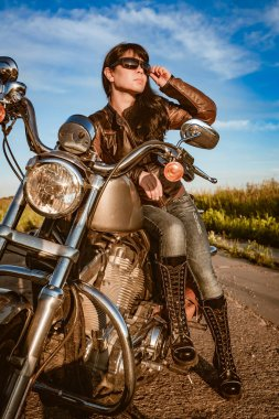 Biker girl in a leather jacket and sunglasses sitting on motorcycle