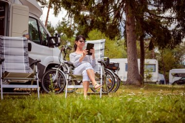 Woman looking at the tablet near the camping . Caravan car Vacation. Family vacation travel, holiday trip in motorhome RV. Wi-fi connection information communication technology.