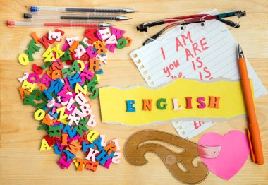 ENGLISH wooden letters and learning stuff near a pile of other letters over wood board background
